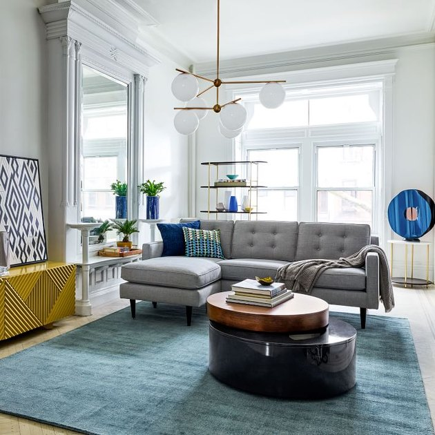 living room space with blue rug and gray couch