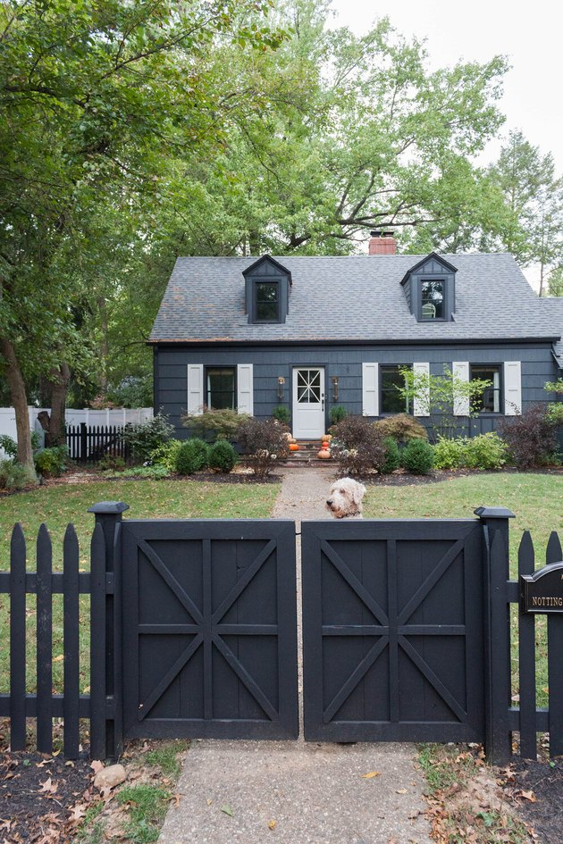 traditional home exterior idea of a dark house with white shutters on the window