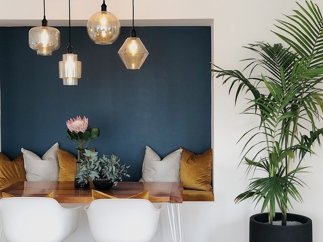 colors that go with blue, dining nook with blue accent wall and gold velvet bench and pillows