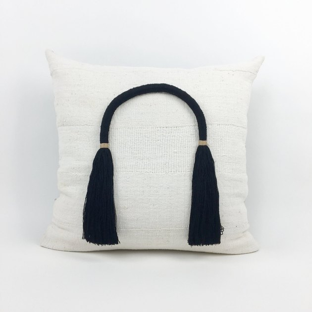 White throw pillow with black arched tassel bonded to front