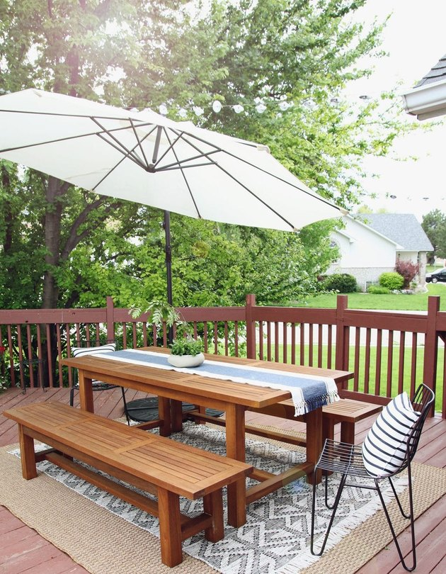 outdoor patio dining area with wood benches and table on top of area rug  with umbrella