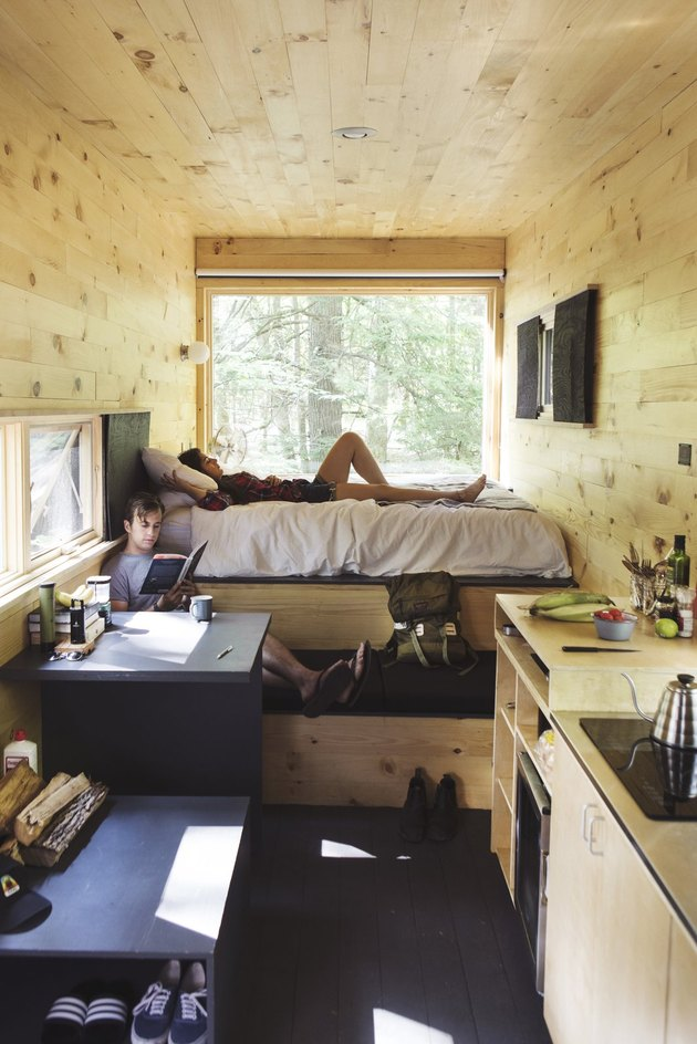 Two men reading in a tiny cabin.