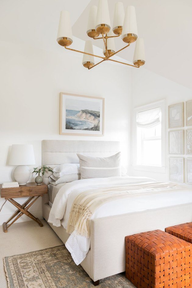 Small bedroom decorating idea in white space with brass chandelier and upholstered bed