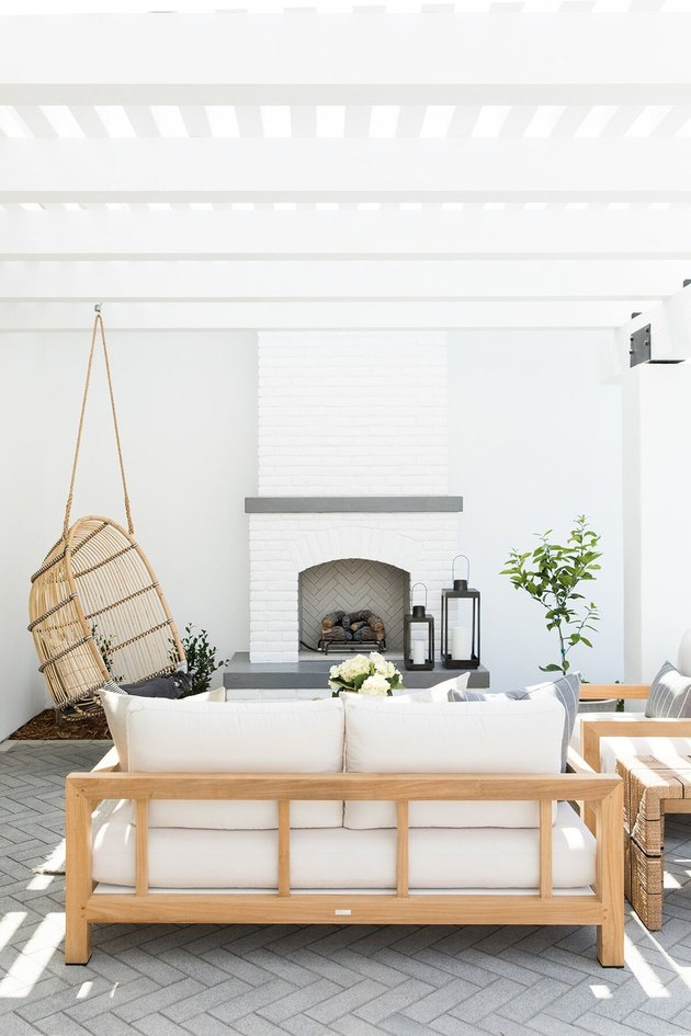 white outdoor patio seating area in front of fireplace with hanging chair and sofas