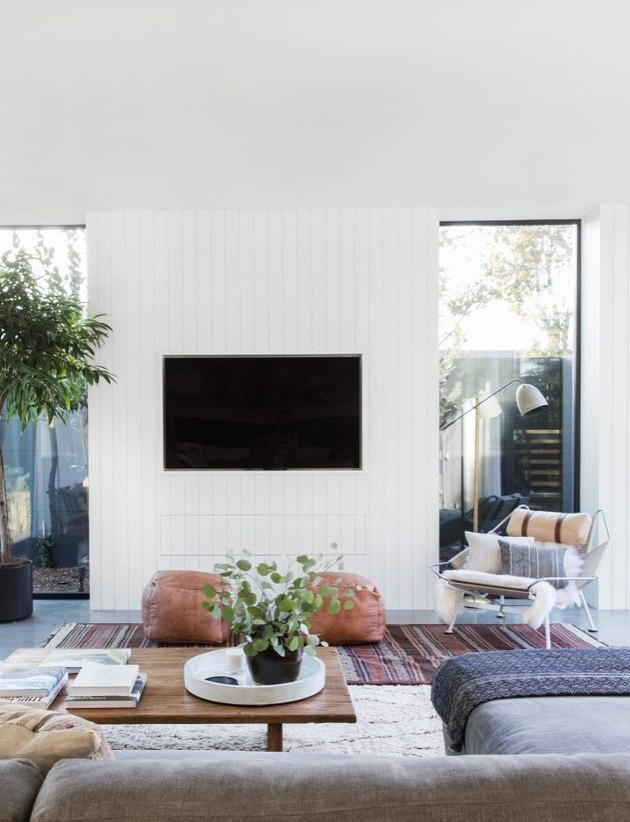living room TV idea with a tile surround flanked by windows