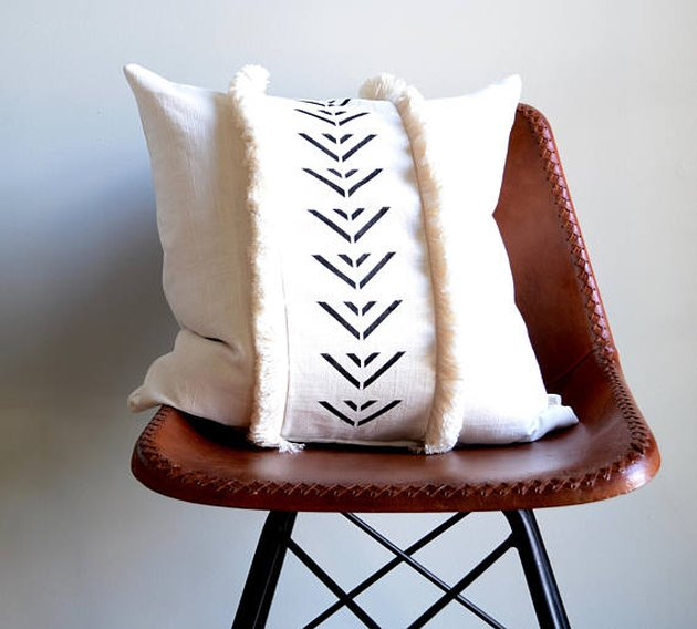 White throw pillow featuring black geometric and fringe accents