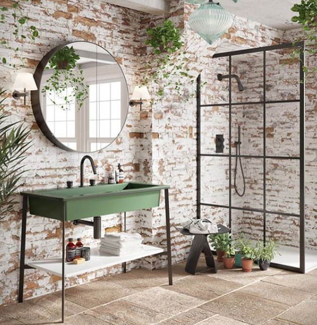 green bathroom sink idea with brick walls and round mirror