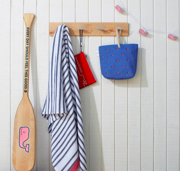 an oar next to hooks showing a towel and bags