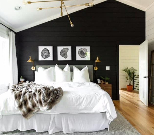 Black paneled accent wall, white bedding, gray headboard, brass modern chandelier, light wood floors, brass sconces, black and white art above bed, faux fur throw with rustic colors