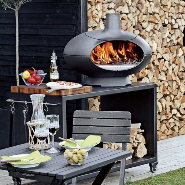 small outdoor kitchen idea with grill and pizza oven next to chopped wood