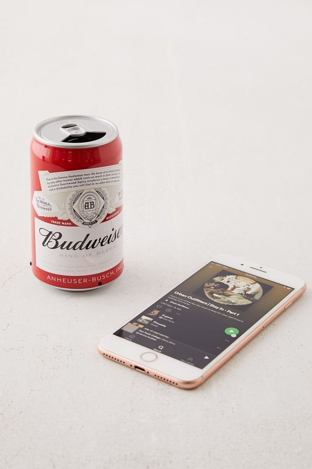 bluetooth speaker in the shape of a beer can near phone
