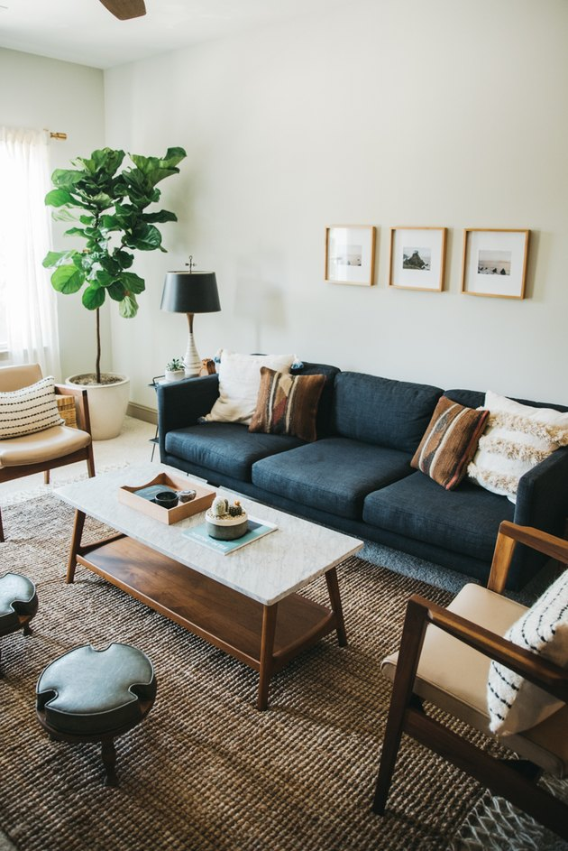 Modern bohemian living room idea with blue sofa and plants