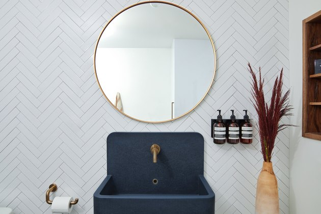 Navy bathroom sink idea with chevron tile backsplash and round mirror