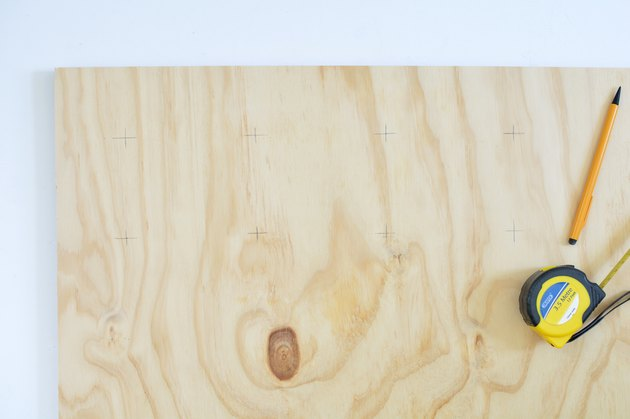 Marking drill holes on plywood sheet