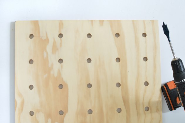 Plywood pegboard with peg holes and drill
