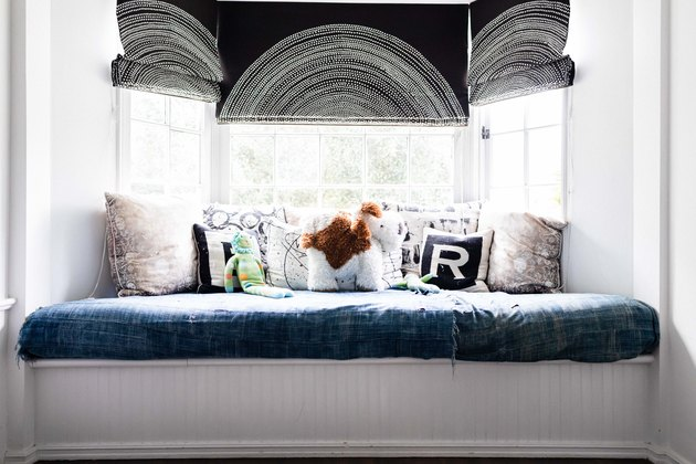 Cushioned reading nook with patterned bay window curtains