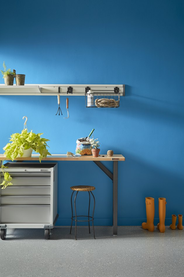 table with plants and a stool and gardening tools hanging above