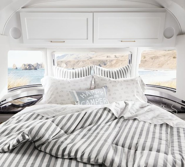 bed with striped sheets inside of an airstream
