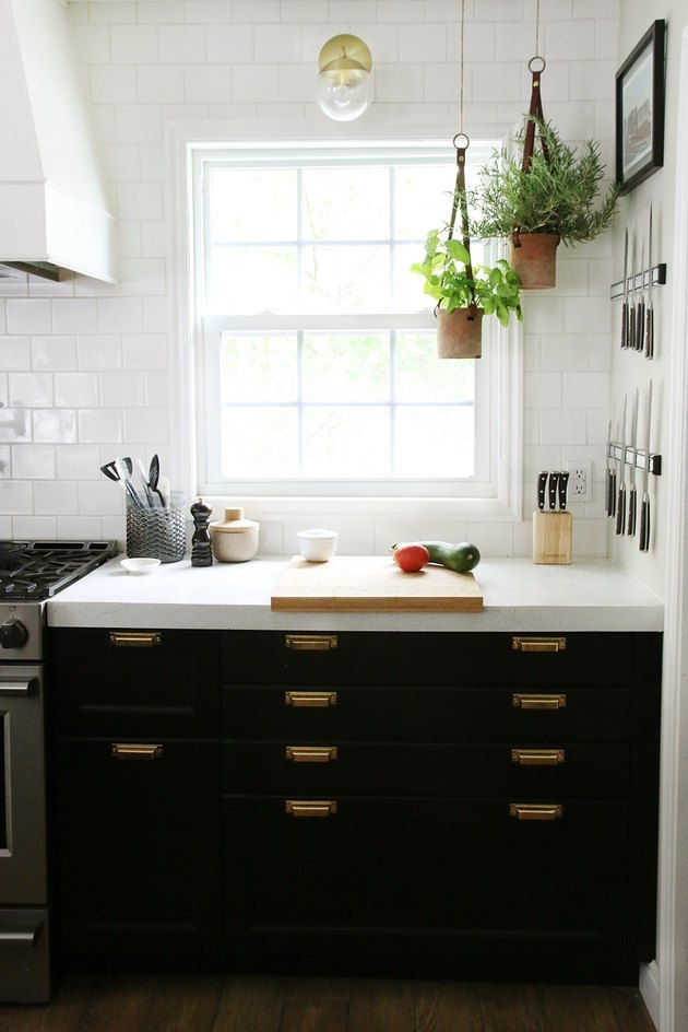 Traditional double-hung kitchen window in kitchen with black cabinets and white tile