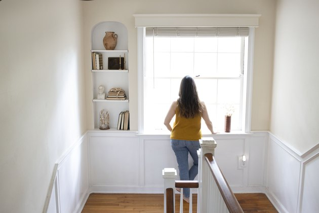Woman looking out of a bay window