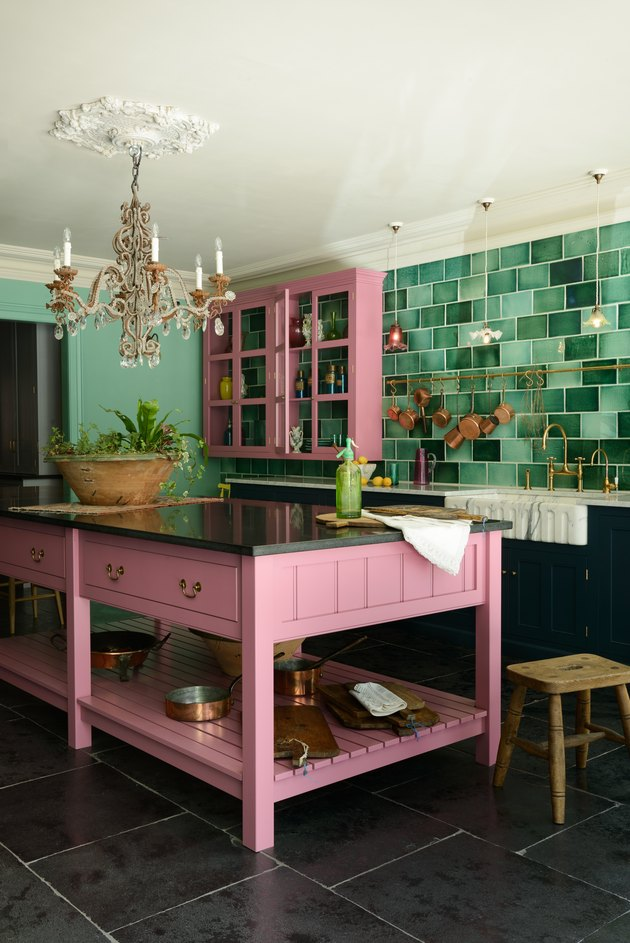 maximalist kitchen with green backsplash and pink cabinets and crystal chandelier