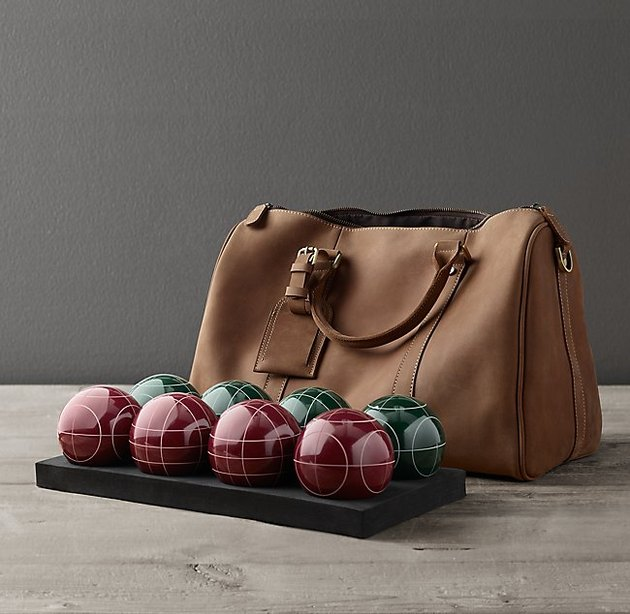 The bocce set next to a leather bag