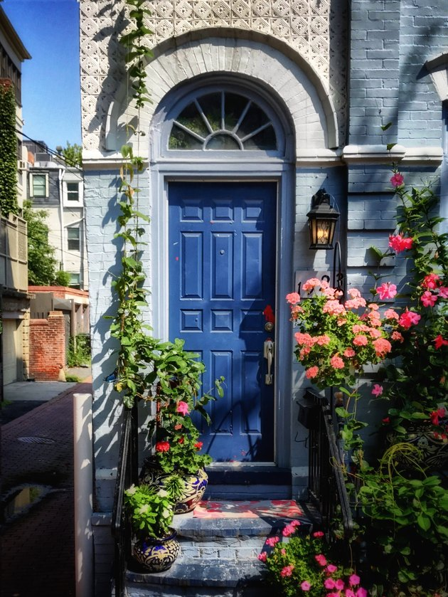 blue traditional front doors with arched transom and flowers