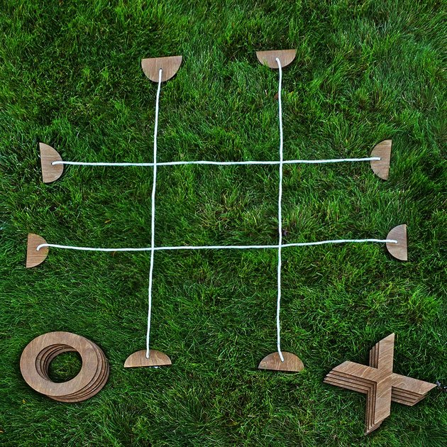 Tic tac toe parts spread out in the grass