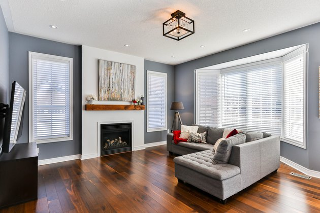 Gray living room with white fireplace and blinds for bay window curtains