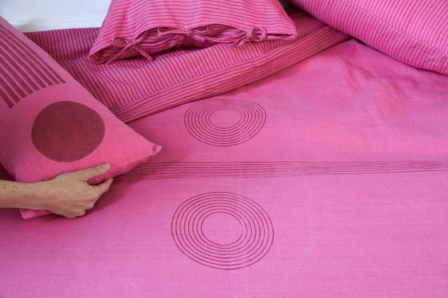 person holding a pink pillow over pink sheets