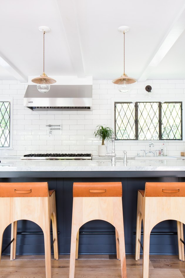 Muntin kitchen window in a vintage-modern kitchen with a blue island and white subway tiles