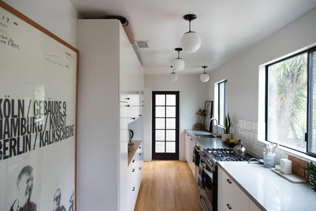 Simple metal kitchen windows in kitchen with white globe pendant lights and white cabinets