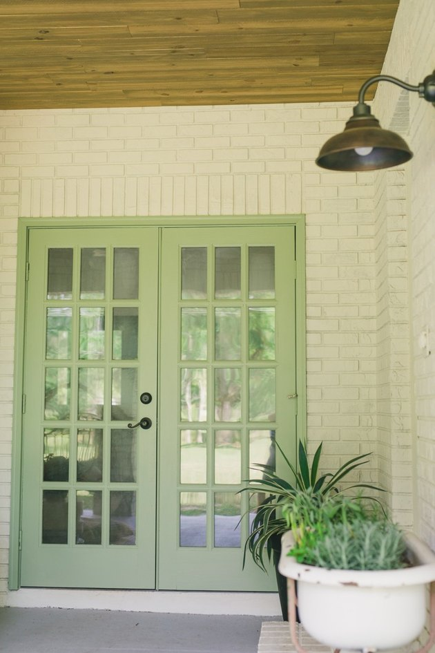 Patio French doors painted in sage color and surrounded by white brick