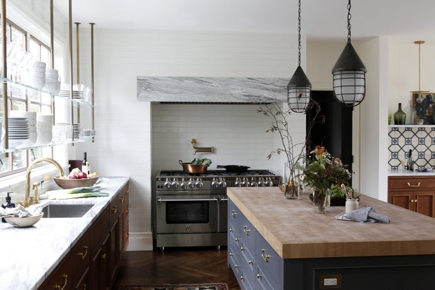 Open shelving in front of traditional kitchen windows in kitchen with dark island