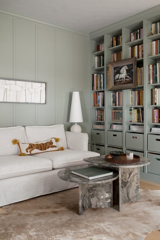 Modern den with sage color walls and bookshelf
