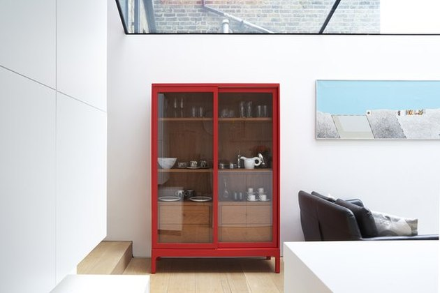 White modern room with large skylight, painting, light wood floors and vermillion color display cabinet with glass doors.