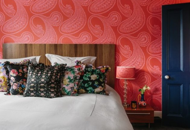 vermillion color wallpaper, wood headboard, floral throw pillows, navy blue door, lamp with red patterned lampshade.