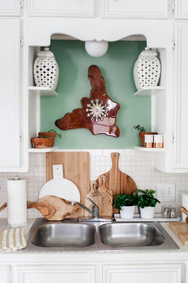 Cuisine vintage avec armoires blanches et alcôve de couleur sauge peinte