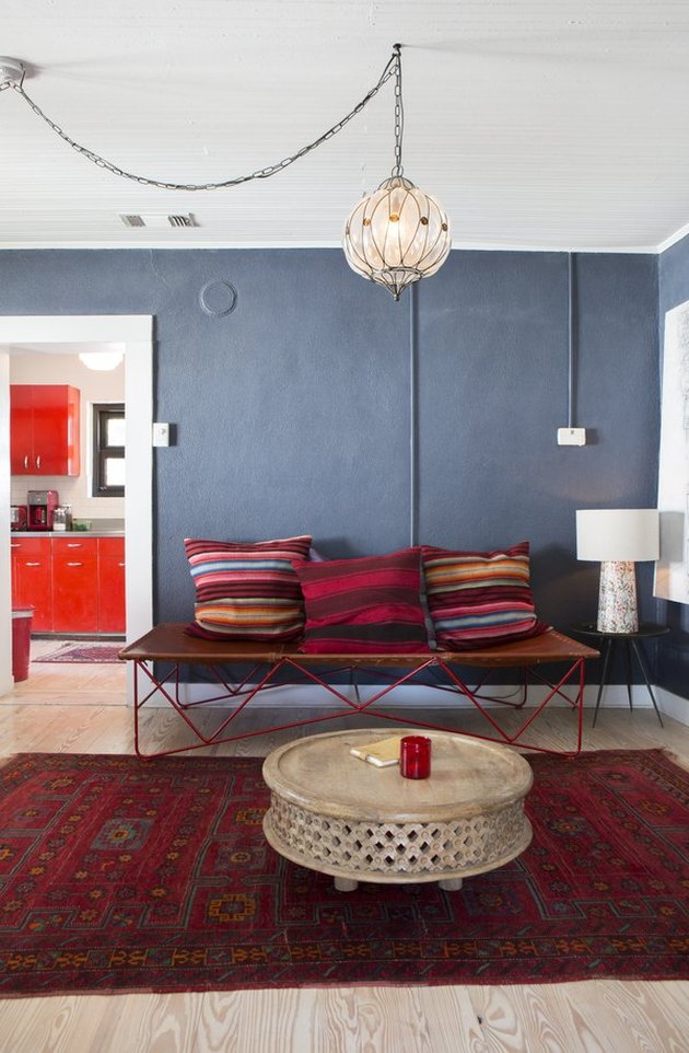 Slate blue walls, bohemian pendant, vermillion color area rug, with red textile throw pillows, leather bench, white shade table lamp, round coffee table.