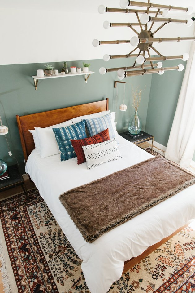 Bohemian guest room with a sage color accent wall and brass chandelier