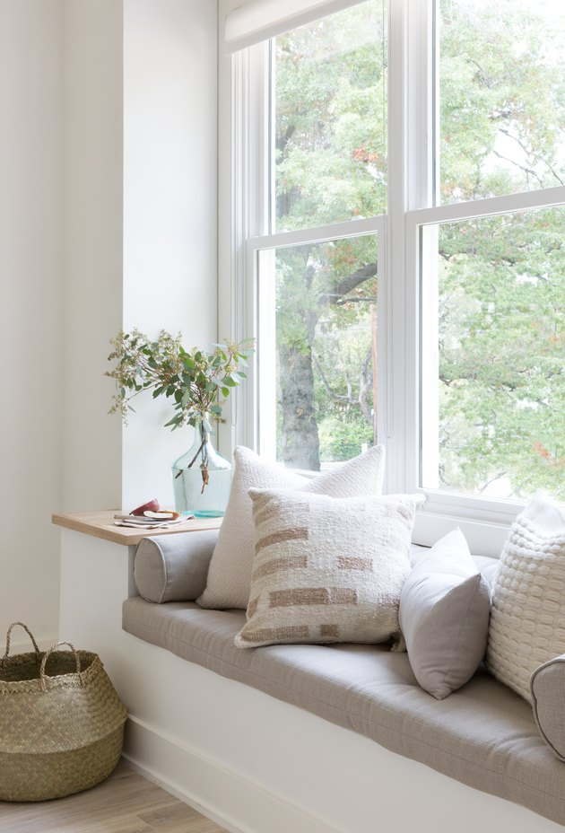 white nook with window bench seating with pullows