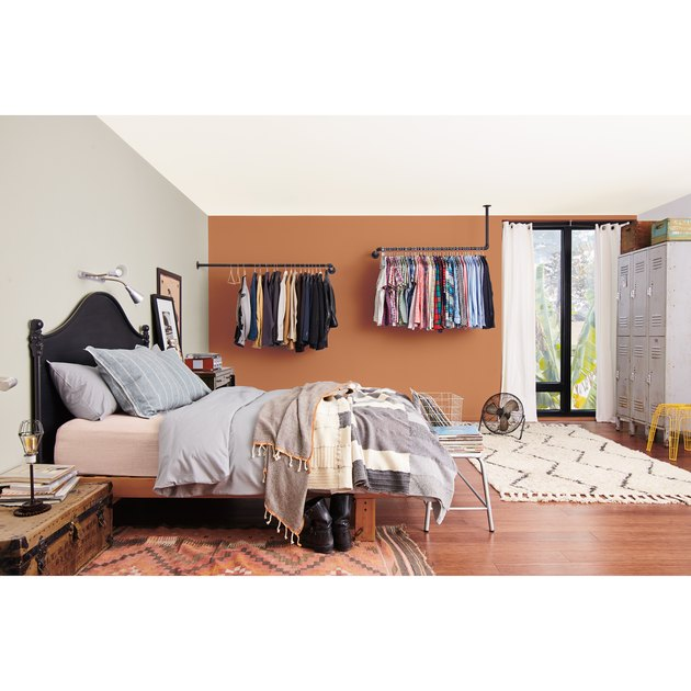 bedroom space with a bed and hanging clothes