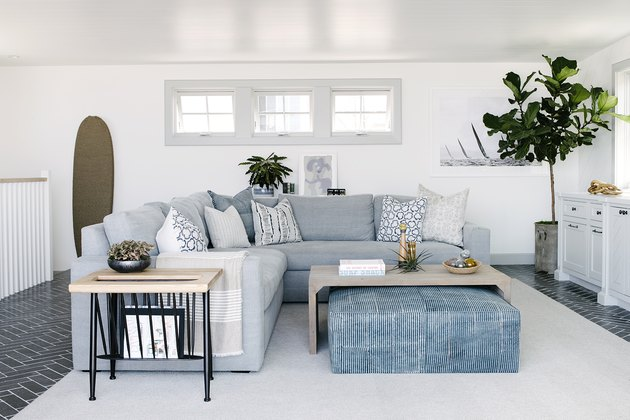 White and blue modern living room with sectional sofa and large ottoman
