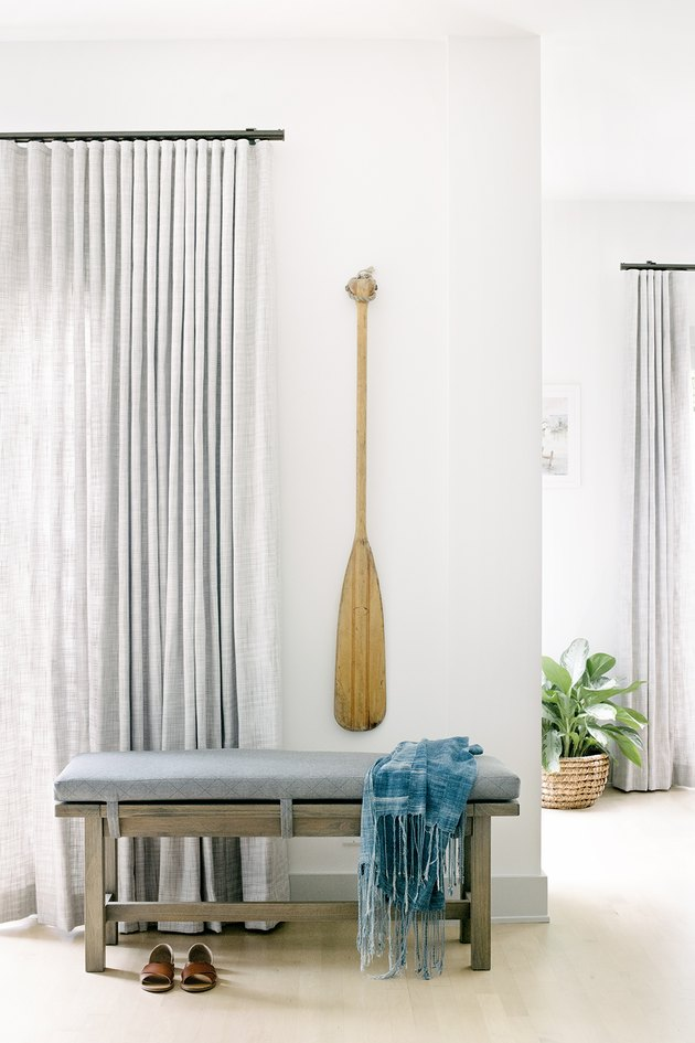 Vintage oar hung on white wall above accent bench