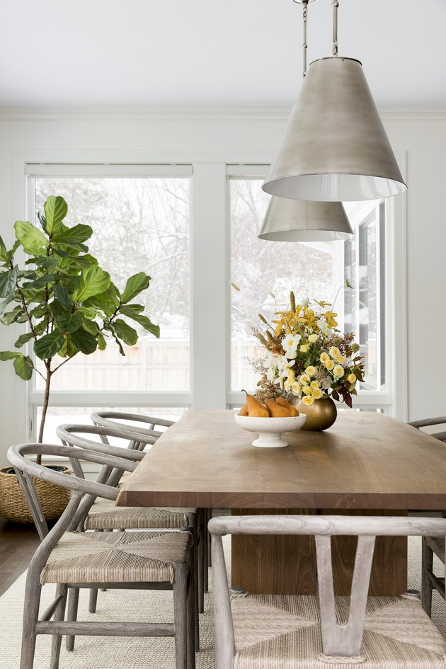 Dining table with potted tree near window and hanging pendant lights