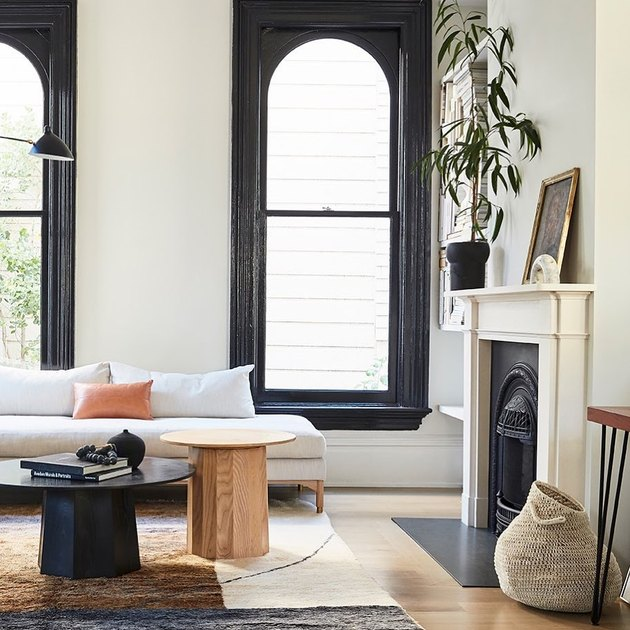 black windows in living room with black coffee table and white fireplace
