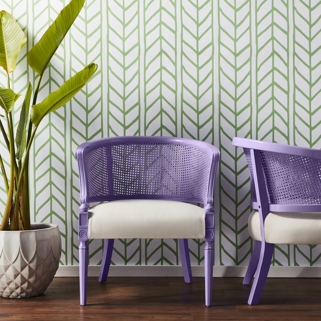 two purple chairs with a plan nearby and a white and green chevron wall