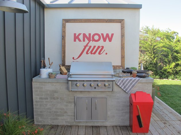 Outdoor kitchen with red and white sign above grill
