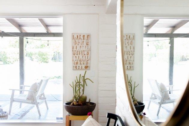 A corner reveals interior adobe walls and a local artist's work.