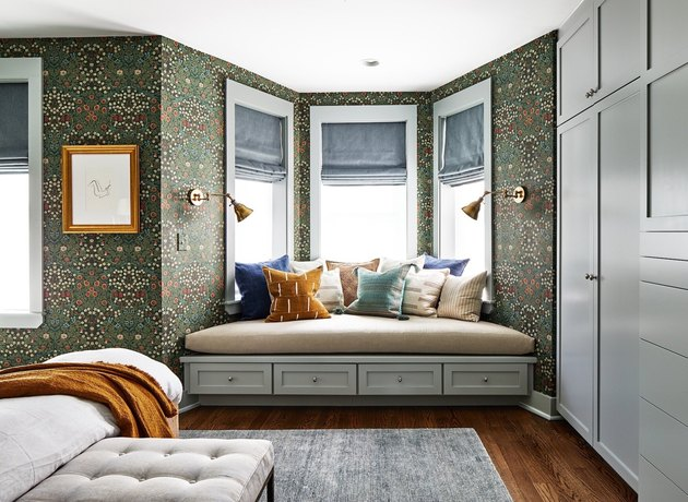 green wallpapered bedroom with bay window bench seating with pillows